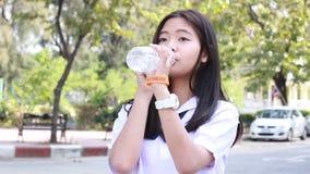 A menina bonita adolescente do estudante tailandês dá a água potável vídeos de arquivo