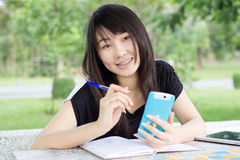 A menina bonita adolescente do estudante tailandês escreve um livro que senta-se no parque Fotografia de Stock Royalty Free