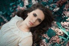 A menina bonita adolescente que encontra-se no lilás floresce o fundo Ascendente próximo do retrato Foto de Stock