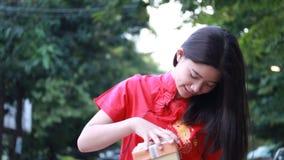 A menina bonita adolescente tailandesa no chinês veste-se, ano novo feliz e presente aberto da caixa, sorriso e muito feliz video estoque