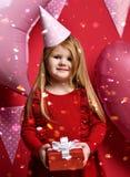 Menina bonita adorável com balões cor-de-rosa e o presente do vermelho e o tampão atuais do aniversário Imagem de Stock Royalty Free