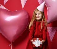 Menina bonita adorável com balões cor-de-rosa e o presente do vermelho e o tampão atuais do aniversário Fotos de Stock