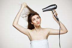 Menina bonita alegre no canto de riso de sorriso de toalha com o secador de cabelo que faz a cara engraçada sobre o fundo branco fotografia de stock