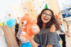 A menina bonita alegre no chapéu festivo verde é satisfeito com o urso de peluche no feriado do aniversário Fotografia de Stock Royalty Free