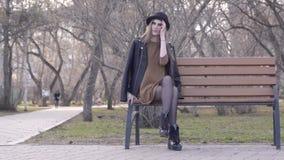 Menina bonita alegre no chapéu que senta-se no banco no parque ensolarado do outono a??o Jovem mulher bonita no chapéu que senta- filme