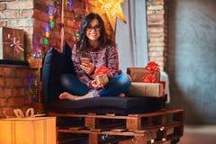 Menina bonita alegre que guarda um telefone ao sentar-se em um sofá com caixas de presente em uma sala decorada com interior do s fotos de stock