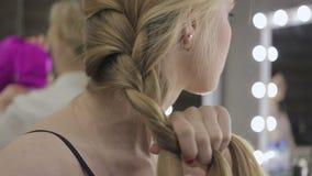 A menina bonita amarra seu cabelo nas tranças, conceito do cuidado da beleza, conceito da beleza video estoque