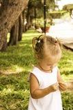 A menina bonita anda no parque guarda uma flor e olha-o Fotos de Stock Royalty Free