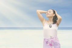 A menina bonita aprecia a luz do sol na praia Fotografia de Stock