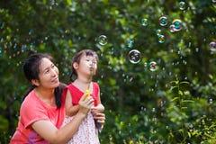 Menina bonita asiática e suas bolhas de sabão de sopro da mãe Família dentro Fotos de Stock