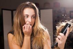 Menina bonita assustado que descobre a queda de cabelo em uma escova de cabelo imagem de stock royalty free