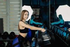 A menina bonita ativa do modelo da aptidão toma pesos das cremalheiras para malhar no gym foto de stock royalty free