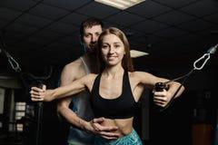 A menina bonita ativa do modelo da aptidão treina os músculos peitorais no simulador junto com um instrutor no gym foto de stock