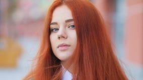 Menina bonita atrativa com cabelo vermelho no t-shirt branco e no revestimento marrom do negócio que olham delicadamente na câmer video estoque