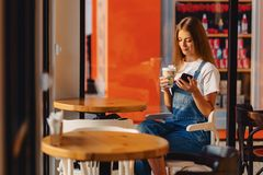 Menina bonita atrativa nova no café com café e telefone no mo foto de stock royalty free