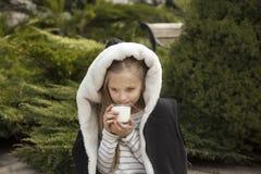 A menina bonita bebe o leite de um vidro Imagem de Stock Royalty Free