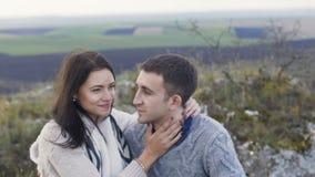 A menina bonita beija seu homem considerável na rocha lentamente video estoque