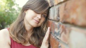 Menina bonita bonito nova perto do smilng e de flertar da parede de tijolo vermelho, mulher romântica sonhadora que anda fora, em filme