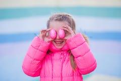 Menina bonita bonito que joga com os ovos coloridos para a celebração da Páscoa Fotos de Stock Royalty Free