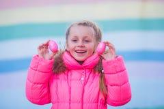 Menina bonita bonito que joga com os ovos coloridos para a celebração da Páscoa Imagens de Stock Royalty Free
