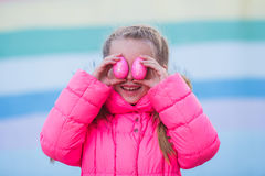 Menina bonita bonito que joga com os ovos coloridos para a celebração da Páscoa Fotos de Stock