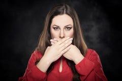 A menina bonita cobre sua boca com sua mão foto de stock royalty free