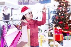Menina bonita com a árvore de Natal na loja de roupa Foto de Stock