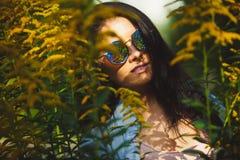 A menina bonita com étnico caucasiano veste óculos de sol redondos à moda na natureza Fotografia de Stock Royalty Free