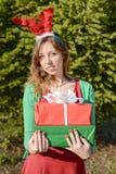 Menina bonita com as orelhas da rena que guardam presentes de Natal Imagens de Stock