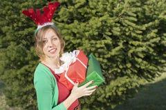 Menina bonita com as orelhas da rena que guardam presentes de Natal Fotos de Stock Royalty Free