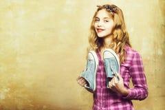 Menina bonita com as sapatilhas azuis da forma nas m?os foto de stock royalty free