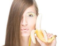 Menina bonita com a banana isolada no branco. Imagem de Stock