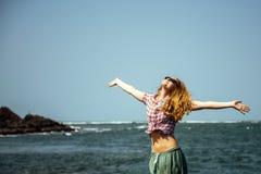 Menina bonita com a barriga 'sexy' despida que relaxa em rochas do mar fotos de stock royalty free