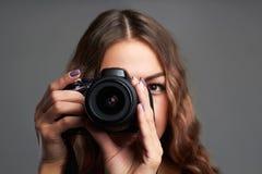 Menina bonita com câmera A mulher bonita é um fotógrafo profissional Imagens de Stock Royalty Free