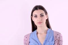 Menina bonita com cabelo atrás de suas orelhas e camisola cor-de-rosa que que olham para a frente Fotografia de Stock