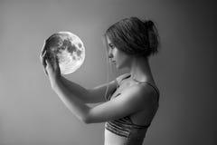 A menina bonita com cabelo branco guarda a lua Fotos de Stock Royalty Free