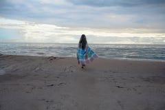 Menina bonita com cabelo branco longo que anda ao longo da areia ao mar Fotografia de Stock
