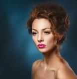 Menina bonita com cabelo e as sardas vermelhos em um fundo azul imagens de stock
