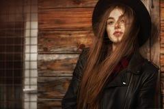Menina bonita com cabelo e o chap?u negro longos, suportes no fundo da casa de madeira velha do vintage fotografia de stock royalty free
