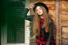 Menina bonita com cabelo e o chap?u negro longos, suportes no fundo da casa de madeira velha do vintage fotos de stock royalty free