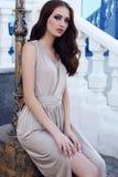 Menina bonita com cabelo escuro e olhos azuis no vestido bege elegante imagens de stock royalty free