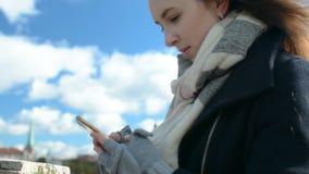 A menina bonita com cabelo longo bonito texting, usando o smartphone do telefone celular com a cidade velha no fundo filme