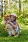 A menina bonita com cabelo longo em um chapéu anda com seu cachorrinho do animal de estimação e delicadamente aperto de seu dia d Fotografia de Stock