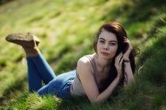 A menina bonita com cabelo longo encaracolado encontra-se na grama verde Fotos de Stock Royalty Free