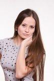A menina bonita com cabelo longo guarda uma mão no pescoço foto de stock