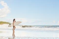 Menina bonita com cabelo longo na praia com prancha Imagem de Stock Royalty Free