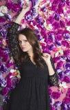 Menina bonita perto da parede com flores violetas imagens de stock royalty free