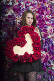 Menina bonita perto da parede com flores violetas foto de stock royalty free