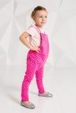Menina bonita com cabelo louro, em macacões cor-de-rosa no fundo branco Fotos de Stock