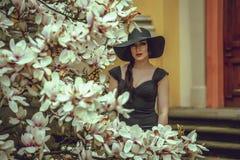 Menina bonita com cabelo preto em um vestido preto em um fundo de uma flor da magnólia Foto de Stock